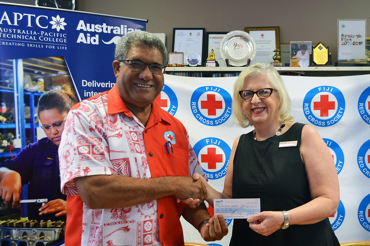 FRCS Director General, Mr Filipe Nainoca receives cheque from APTC Executive Director - SME, Ms Carol-Anne Blecich